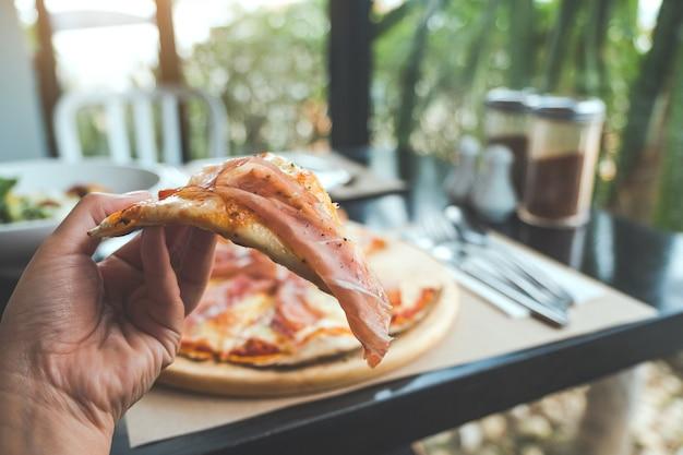 Une main cueillant un morceau de pizza au jambon de parme pour manger au restaurant Photo Premium