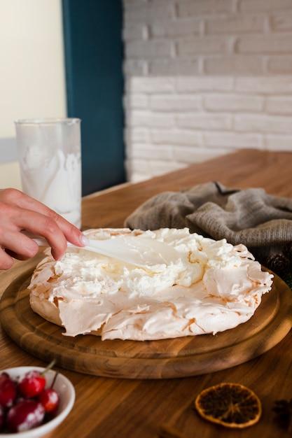 Main avec une cuillère décorant le gâteau meringue Photo gratuit