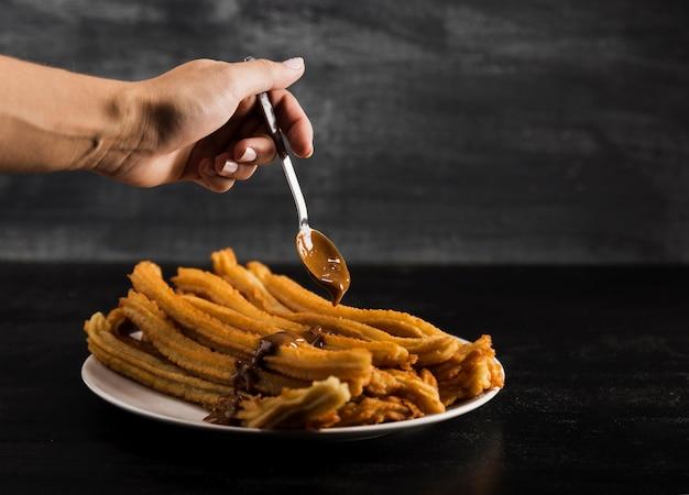 Main et cuillère avec de délicieux churros frits Photo gratuit