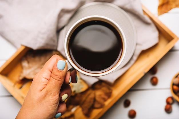 Main de culture tenant le café sur le plateau Photo gratuit