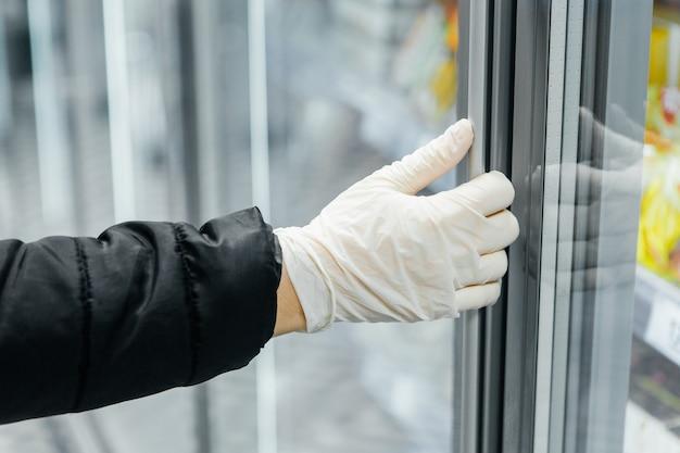 La Main Dans Un Gant Blanc Ouvre Une Porte De Vitrine. Sécurité épidémique Photo Premium