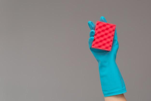 Main dans un gant en caoutchouc contient une éponge de lavage de couleur sur fond neutre Photo Premium