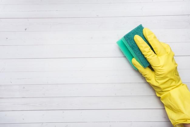 La main dans le gant jaune et l'éponge de nettoyage pour le nettoyage sur fond en bois. Photo Premium
