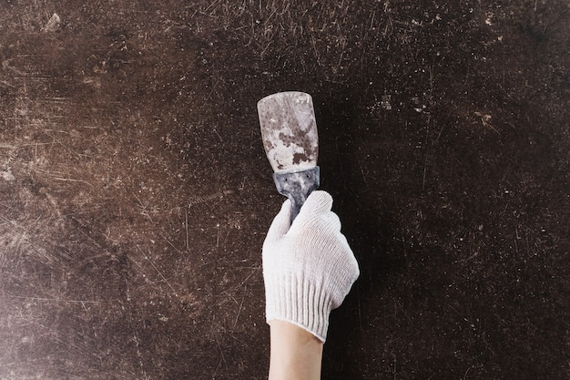 Une Main Dans Des Gants De Travail Avec Une Spatule Sur Un Fond De Marbre Foncé. Faire Des Métamorphoses Photo Premium