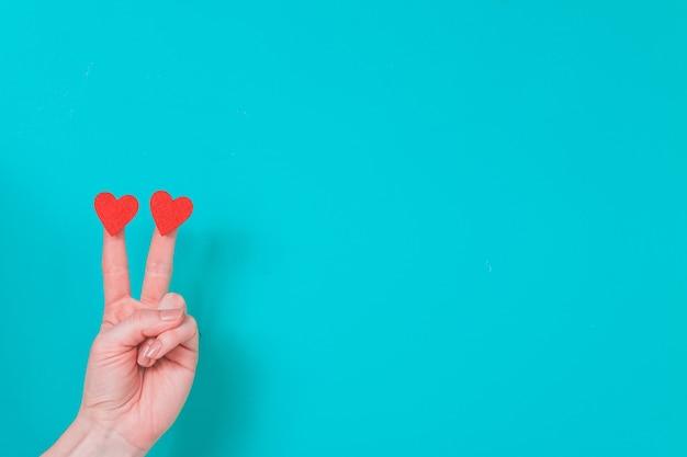Main avec deux doigts avec deux coeurs sur un fond bleu Photo gratuit