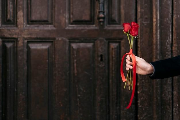 Main Donnant Le Bouquet De Roses Rouges à Son Couple Avec Espace Copie Photo gratuit