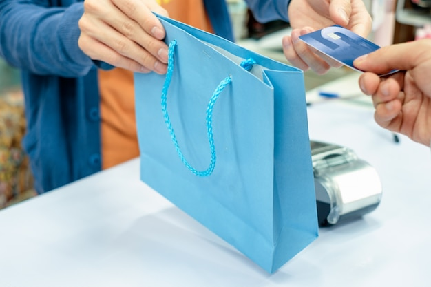 Main donnant la carte de crédit et prendre le sac en papier du caissier du personnel en magasin Photo Premium