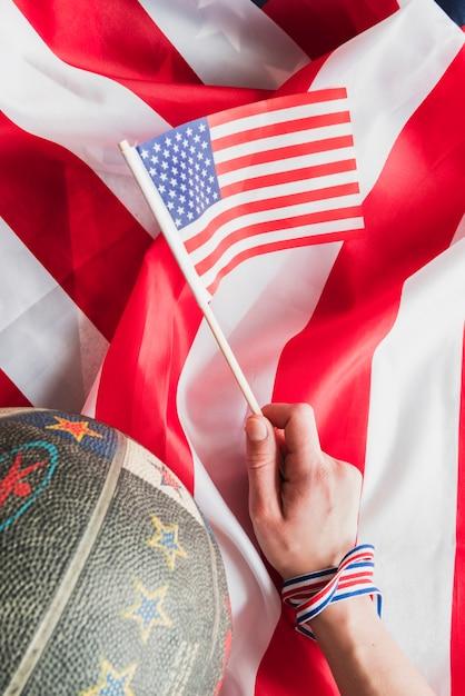Main avec drapeau des états-unis et basket Photo gratuit