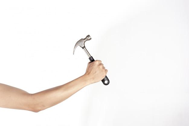 Main droite tenant un marteau, isolé sur fond blanc, concept de fête du travail Photo Premium