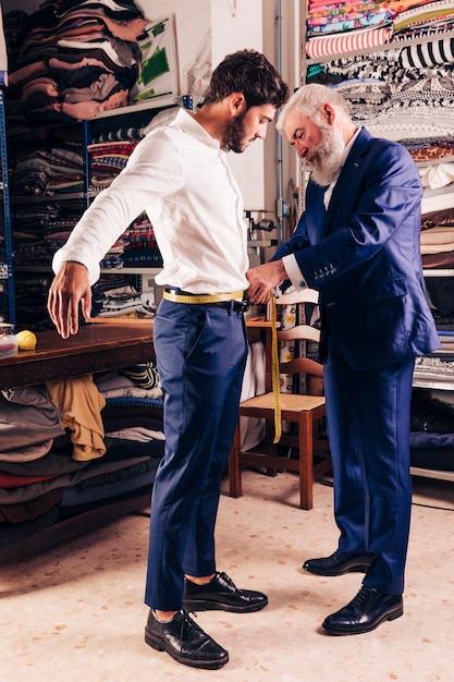 Main du créateur de mode senior prenant la mesure de la taille de son client avec un ruban à mesurer jaune Photo gratuit