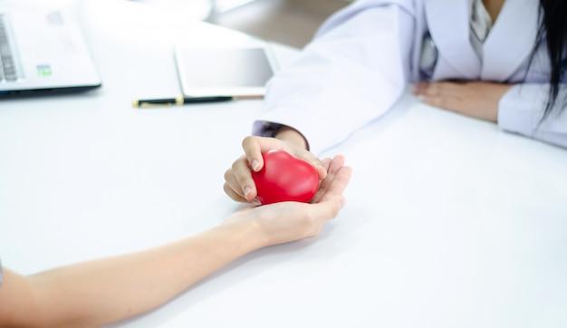 Main du docteur donne le coeur à la main des gens Photo Premium