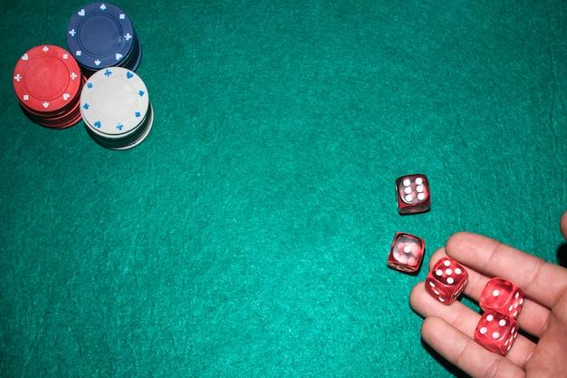 La main du joueur de poker lançant des dés rouges sur la table de poker Photo gratuit