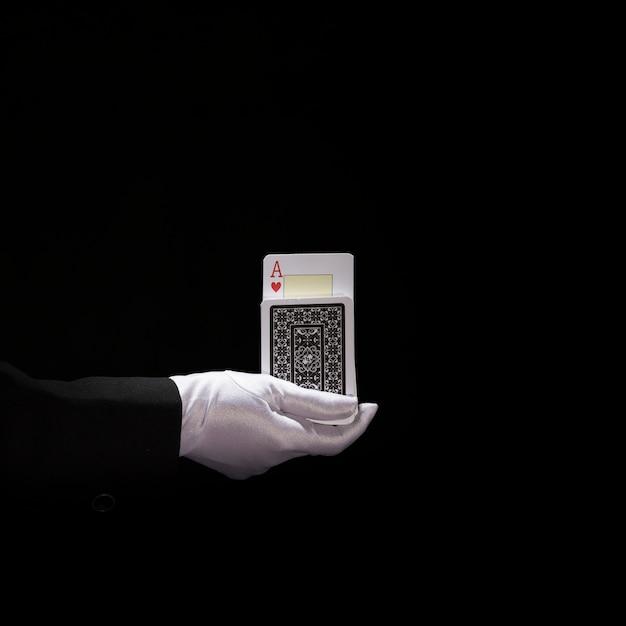 La main du magicien portant des gants blancs effectuant un tour sur les cartes à jouer Photo gratuit