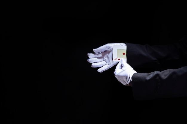 La main du magicien retirant la carte à jouer des as de la manche sur fond noir Photo gratuit