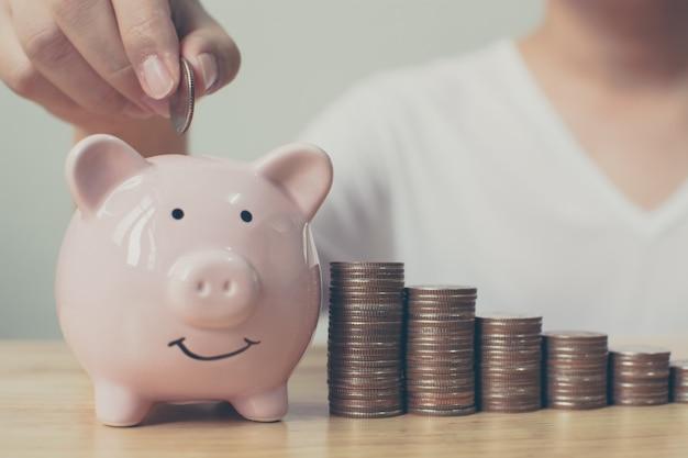 Main du mâle mettant des pièces de monnaie dans la tirelire avec la pile d'argent étape croissante croissance économiser de l'argent. concept d'investissement en entreprise Photo Premium