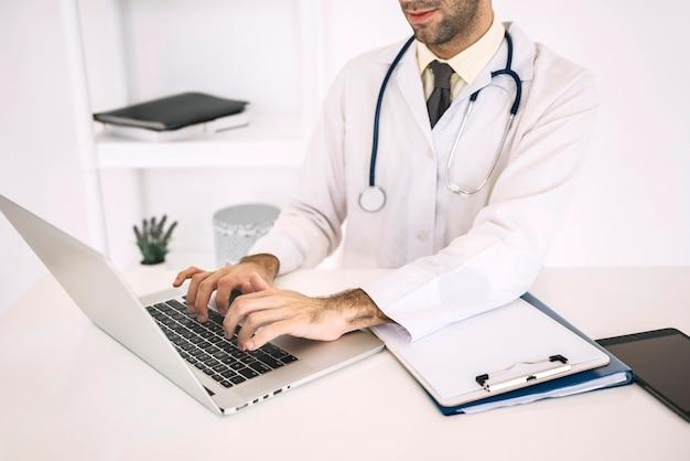 Main du médecin à l'aide d'un ordinateur portable sur le bureau Photo gratuit