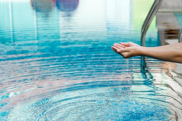 La main et l'eau touchent l'eau bleue. pour actualiser le concept de jouer de l'eau propre avec un espace copie. Photo Premium