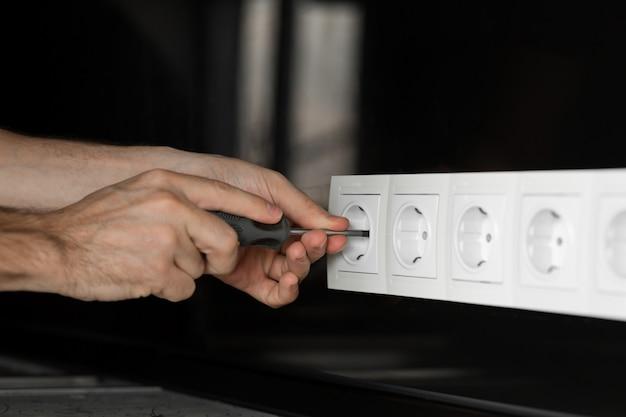 Main d'électricien avec un tournevis démontant une prise électrique blanche sur un mur de verre noir. Photo Premium