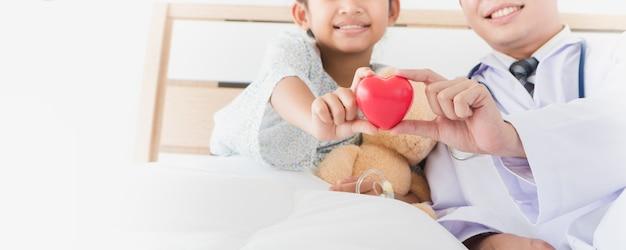 La main de l'enfant asiatique et le médecin de sexe masculin tiennent le coeur rouge allongé sur le lit à l'hôpital. Photo Premium