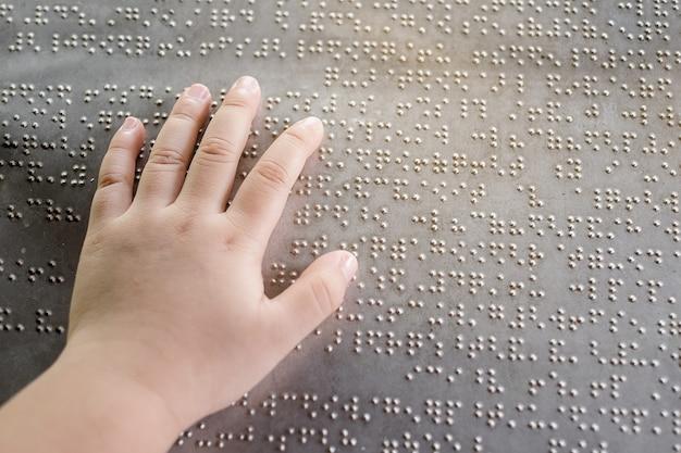 La main de l'enfant aveugle et les doigts touchant les lettres en braille sur la plaque de métal Photo Premium