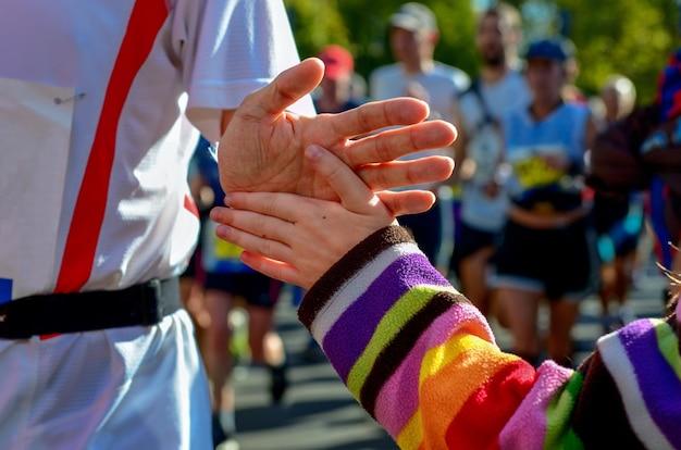 La Main De L'enfant Donnant Un High Cinq Dans Une Course De Marathon Photo Premium