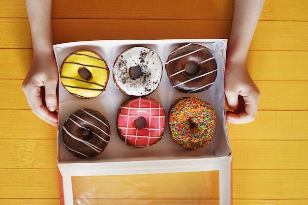 Main d'enfant tenant la boîte avec le dessert de beignet sucré. Photo Premium