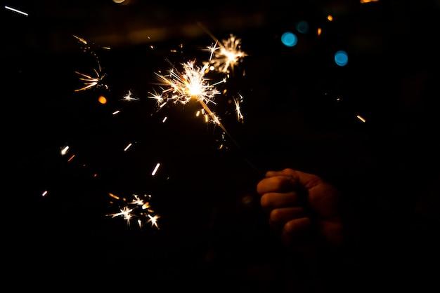 La main de l'enfant tenant un sparkler qui grésille et brille pendant la nuit. Photo Premium