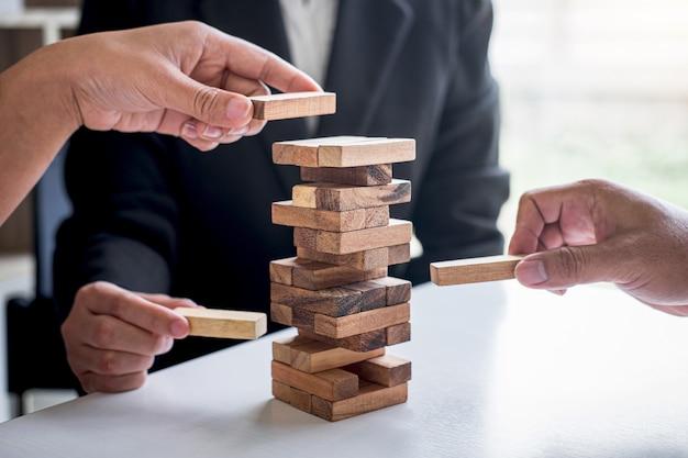 Main de l'équipe commerciale coopérative jouant plaçant la hiérarchie de bloc en bois sur la tour Photo Premium