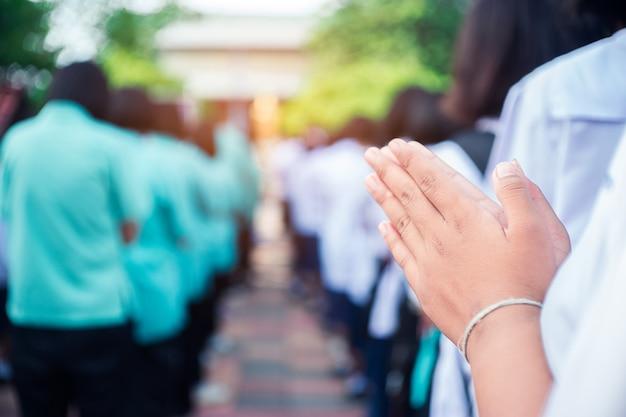La main des étudiants asiatiques rend hommage au bouddha Photo Premium