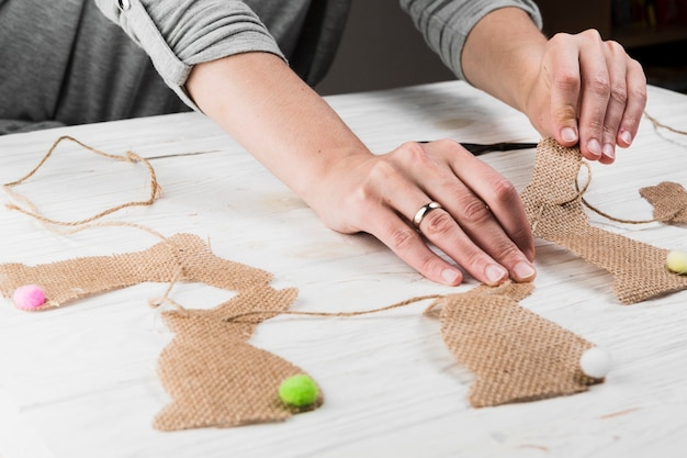 Main faisant la forme de lapin bunting de vêtements de jute sur la table Photo gratuit