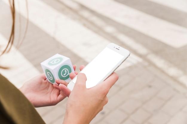 Main féminine à l'aide de téléphone portable et tenant le bloc whatsapp Photo gratuit