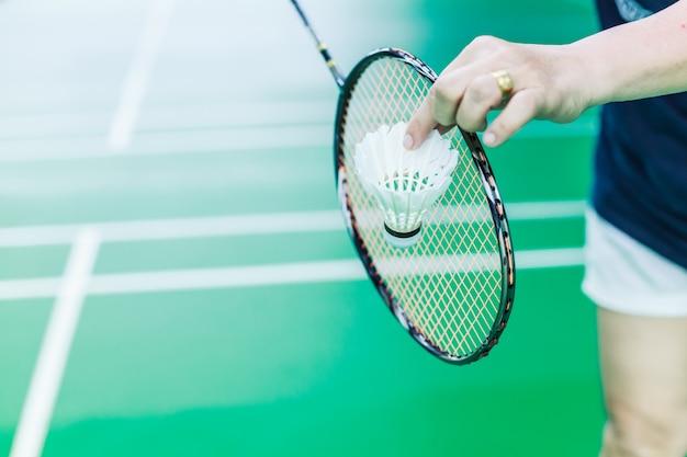 Main féminine de badminton en solo tenant une queue de navette blanche avec une raquette Photo Premium