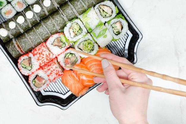 Main féminine avec baguettes et sushi Photo Premium