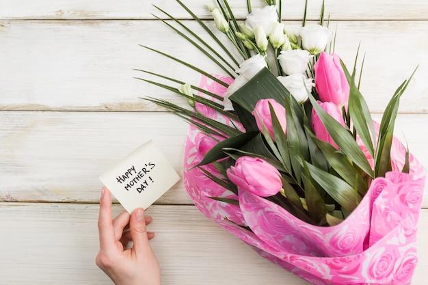 Main féminine avec carte de vœux et bouquet de fleurs Photo gratuit