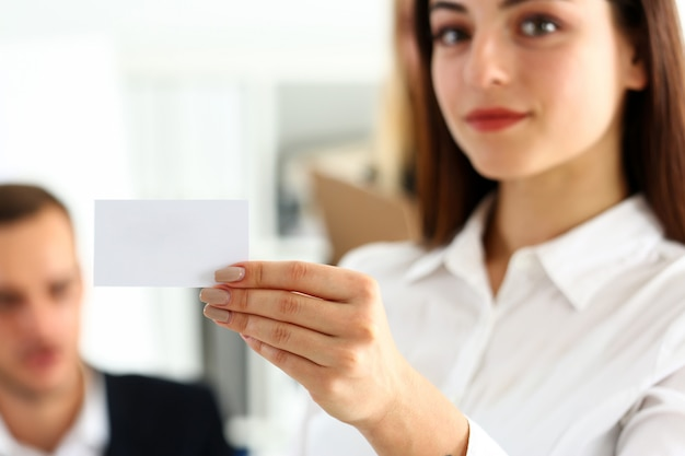 Une main féminine en costume donne une carte de visite vierge au visiteur Photo Premium