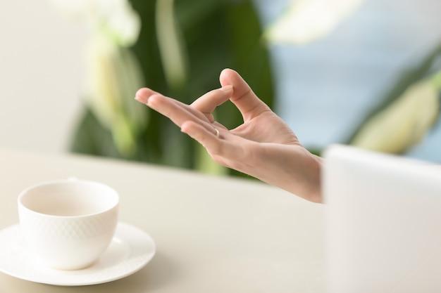 Main féminine dans le geste du menton mudra yogique Photo gratuit