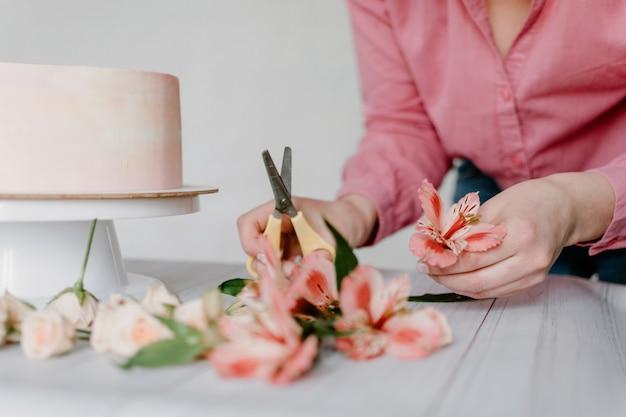 Main Féminine Décorer Le Gâteau D'anniversaire De Mariage Fleur Rose Sur Le Stand. Photo Premium