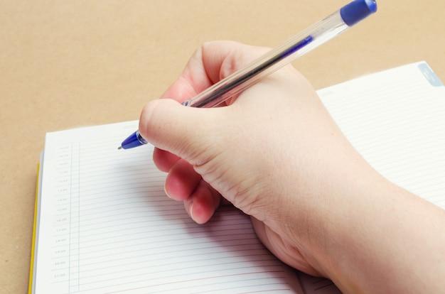 Une main féminine écrit dans un cahier et prend des notes, des plans de la journée, une liste de courses, un gros plan Photo Premium