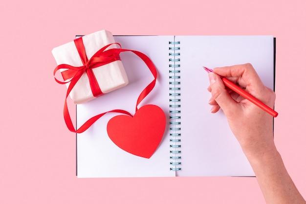 La Main Féminine écrit Un Message D'amour Avec Un Stylo Rouge Dans Un Cahier Ouvert Blanc Blanc Photo Premium
