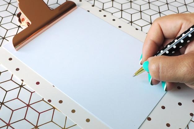 Une main féminine écrit avec un stylo à bille sur une feuille de papier vierge dans un presse-papiers. fond géométrique. Photo Premium