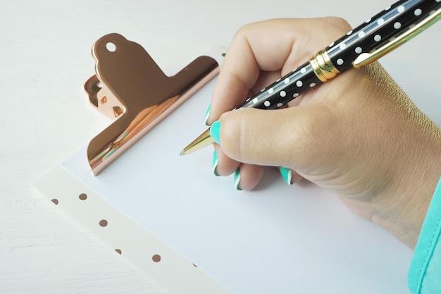 Une main féminine écrit avec un stylo à bille sur une feuille de papier vierge dans un presse-papiers. Photo Premium