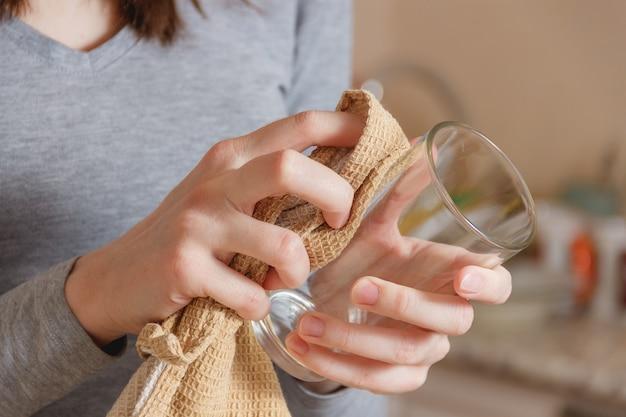 Une main féminine essuie un verre propre de tap in kitchen. Photo Premium