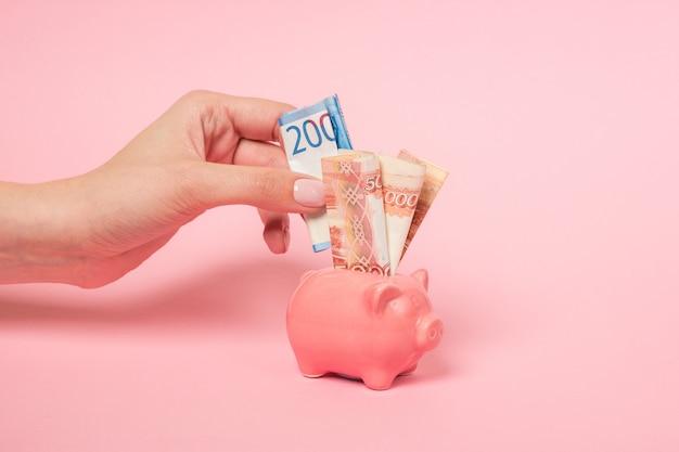 Une main féminine insère un billet de banque en deux mille roubles russes dans une tirelire en céramique rose. Photo Premium