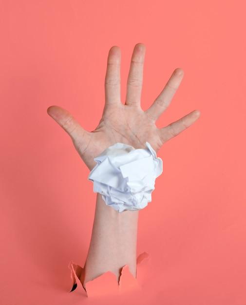 Une Main Féminine Jette Une Boule De Papier Froissé à Travers Le Fond De Papier Rose Déchiré. Concept D'idée Minimaliste Photo Premium