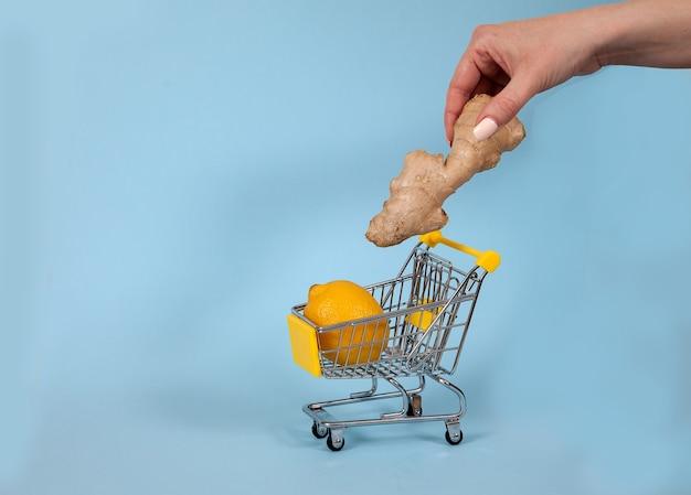Une Main Féminine Met Du Gingembre Dans Un Chariot De Supermarché Photo Premium