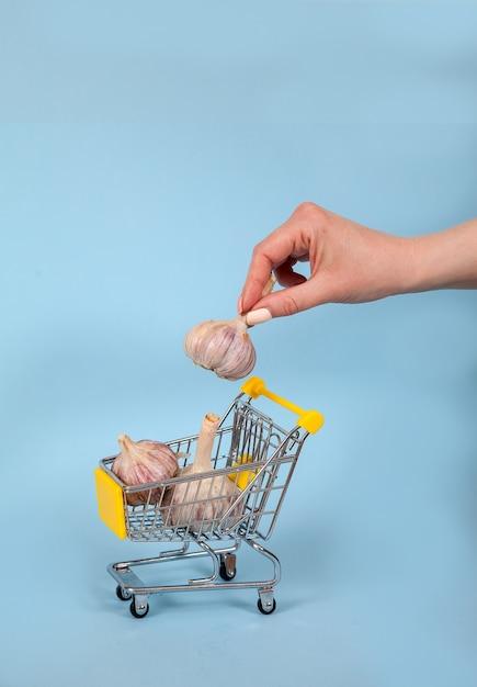Une Main Féminine Met Une Tête D'ail Dans Un Panier De Supermarché Photo Premium