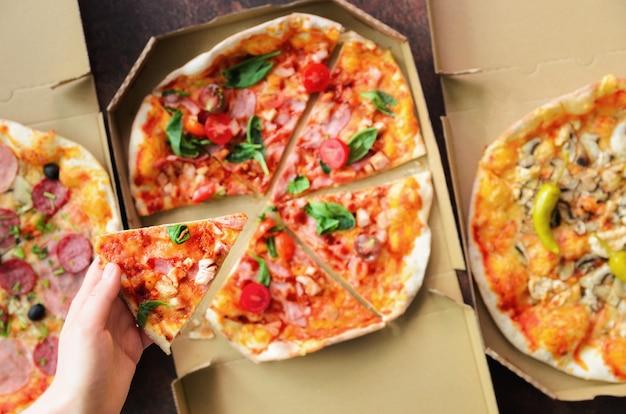 Main Féminine Prenant Une Tranche De Pizza Fraîche De La Boîte De Livraison. Vue De Dessus, Fond Sombre. Mal Bouffe Photo Premium