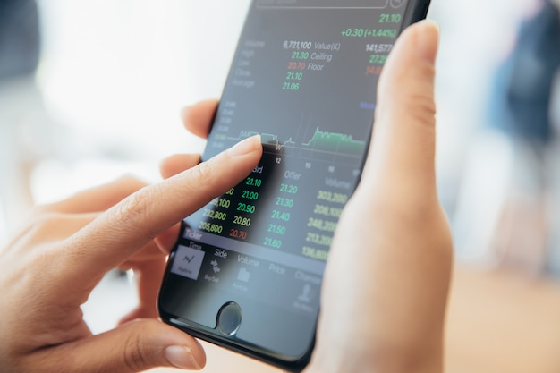 Main féminine avec stock de négoce de smartphone en ligne dans le café-restaurant, concept d'entreprise Photo Premium