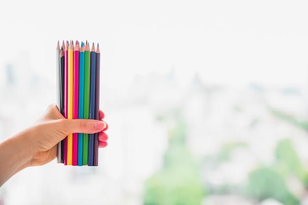 Main féminine tenant ensemble de crayons de couleur sur fond flou Photo gratuit
