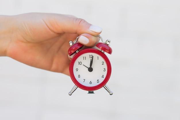 Une main féminine tient un réveil rouge sur la main tendue. notion de temps, sommeil, éveil Photo Premium